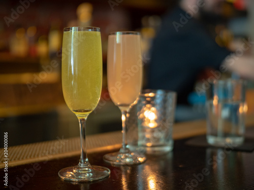 Fotografie, Obraz  Two wineglasses filled with mimosa drinks with bartender in background