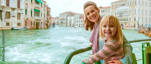 Fototapeta premium Szczęśliwa matka i dziewczynka podróżują weneckim autobusem wodnym