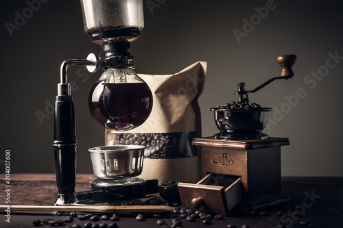 Valokuva  Japanese siphon coffee maker and coffee grinder on old kitchen table