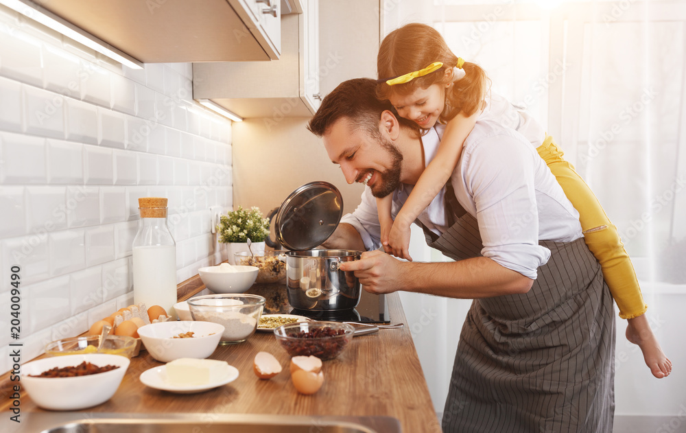 Fototapety, obrazy: happy family in kitchen. Father and child daughter knead dough and bake biscuits