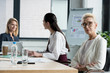 attractive businesswomen sitting at table during meeting in office