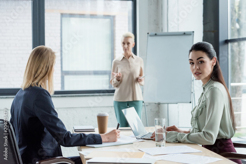Fototapety, obrazy: businesswomen listening to colleague wile she presenting project at meeting in office