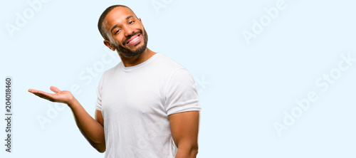 Fotografie, Obraz  African american man with beard holding something in empty hand isolated over bl