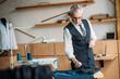 senior tailor examining cloth at sewing workshop