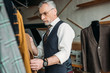 handsome mature tailor examining jackets at sewing workshop