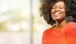 Beautiful african woman confident and happy with a big natural smile laughing, natural expression, outdoor