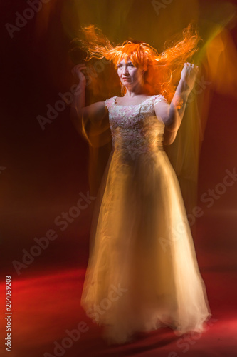 Plagát  Old female actress with orange hair dancing in white dress with light show with