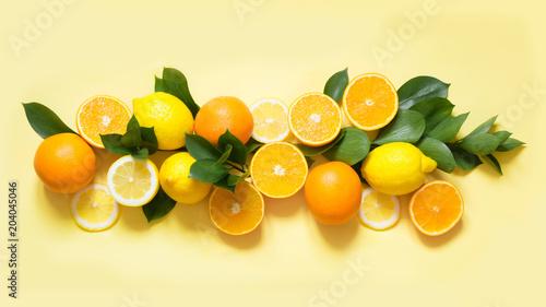 Keuken foto achterwand Vruchten Summer set of tropical fruits, lemon, orange and green leaves on yellow. Banner.