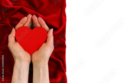 Papiers peints Rouge, noir, blanc Woman's hands holding red heart on red velvet background isolate top view