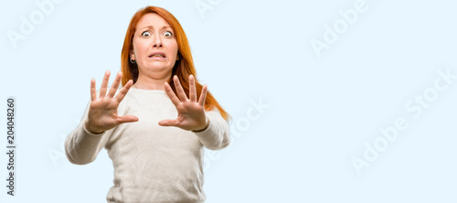 Fotografie, Tablou  Beautiful young redhead woman disgusted and angry, keeping hands in stop gesture