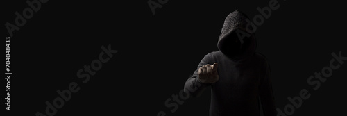 Fotografía  Faceless man in a hood with points a finger at the viewer on a dark background