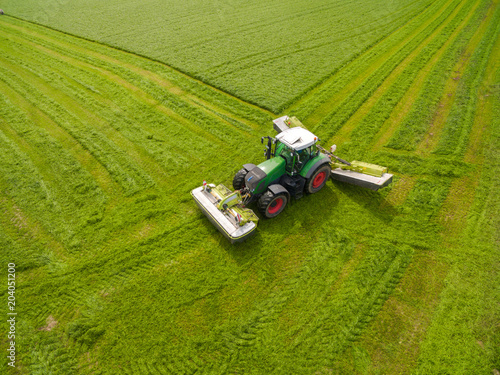 Foto op Canvas Pistache modern tractor working on the agricultural field - tractor plowing and sowing in the agricultural field - aerial view - high top view
