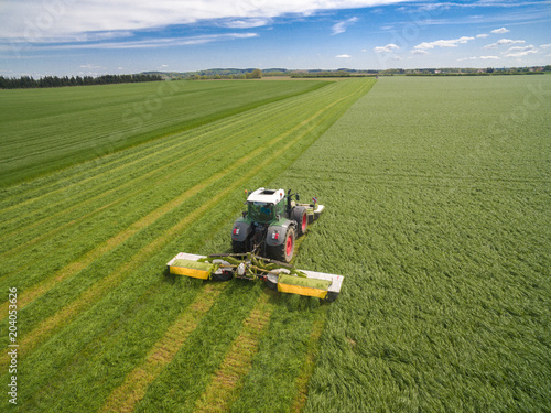 modern tractor working on the agricultural field - tractor plowing and sowing in the agricultural field - aerial view - high top view