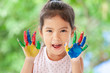 Cute asian little child girl with painted hands smiling with fun and happiness on green nature background