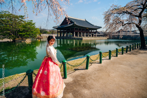 Young asian woman traveler in korean national dress or Hanbok traveling into the Gyeongbokgung Palace with cherry blossom or call sakura in spring with blue sky and clouds at Seoul city, South Korea Poster