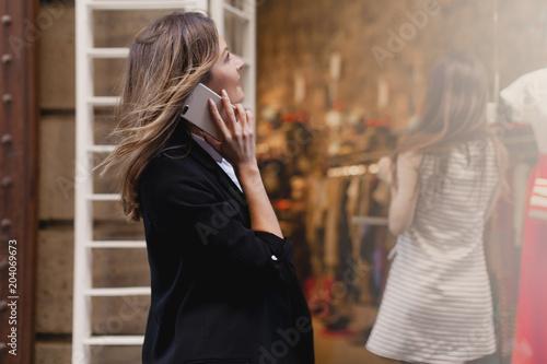 Fotografia Young beautiful woman walking along the street talking via mobile phone and doin