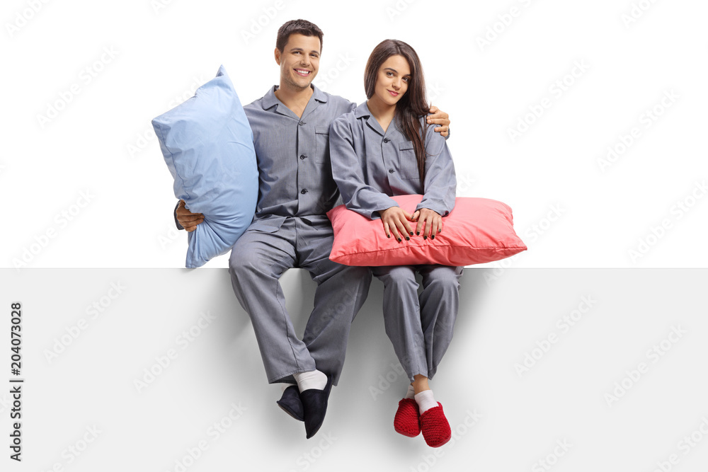 Fototapety, obrazy: Young couple dressed in pajamas sitting on a panel and holding pillows