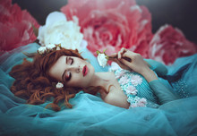 A Beautiful Sensual Girl With Red Hair In A Fairy Blue Lavish Dress As A Sleeping Beauty Lies In Large Flowers Of Pink And White Peonies. The Girl Is A Flower Princess.