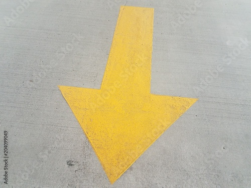 large yellow arrow on grey cement