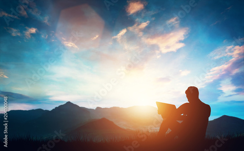 Man sitting with a laptop outdoors in the mountains