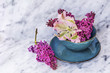 Spring Table Setting with Vintage Blue Cutlery , Lilac Flowers and Pink Tulip on a Marble Background.Floral Table Decor