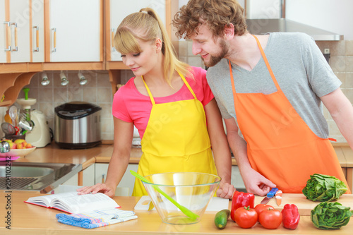 Fotobehang Koken Couple cooking in kitchen reading cookbook