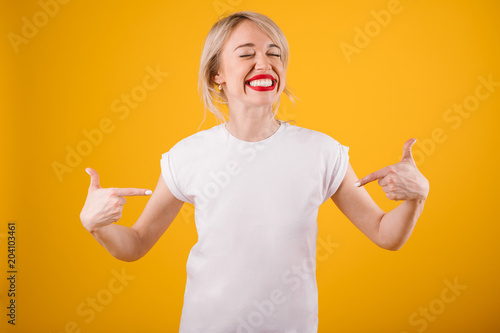 Silly smiling funny woman in white t-shirt where you can place ypur logo text or image. Yellow background
