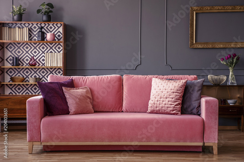 Pink velvet couch with decorative pillows standing in grey living ...