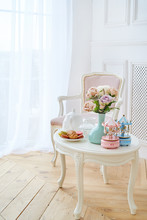 White Wooden Round Table With Breakfast, Flowers And Merry-go-round Musical Carousel With Horses And Pink Soft Chair. Beautiful Modern Interior, Copy Space