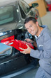Mechanic holding new rear light unit for car, angled