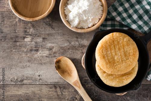 Arepas in iron pan on wooden table. Venezuelan typical food. Top view. Copyspace