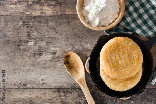 Arepas in iron pan on wooden table. Venezuelan typical food. Top view. Copyspace