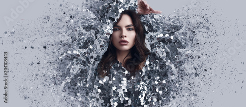 Beautiful brunette woman in fashion dress of sequins with dispersion effect