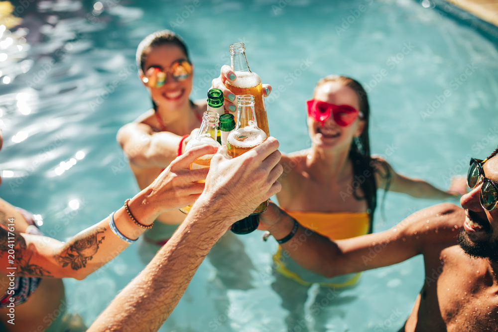 Fototapety, obrazy: Friends enjoying and toasting drinks at pool party
