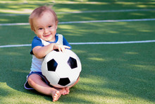 Smiling Infant With A Soccer B...