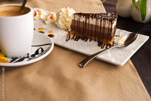 Fotografía  Delicious cake with three different kind of chocolate and cup of coffee