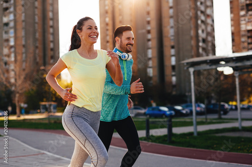 Young attractive couple running outside on sunny day Fototapete