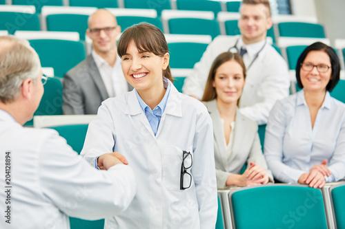 Foto  Dozent gratuliert einer Medizin Studentin