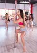 Females pole dancers exercising in studio