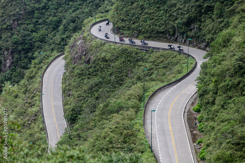 Poster Khaki Speedy motorcycles on road in the mountains with beautiful landscape