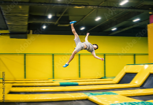 trampoline jumper performs complex acrobatic exercises and somersault on the trampoline.