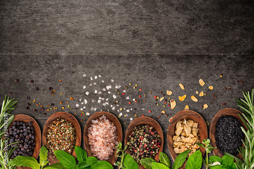 Foto op Plexiglas Kruiderij Various colorful herbs and spices on grey concrete background.