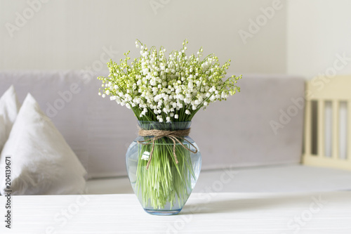 Living room interior design with still life, blossom lily of the valley in vase