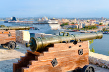 Old Cannons Facing The City Of Havana With An Modern Cruise Ship