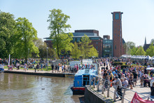 Large Crowd Of People Gather In Front Of The RSC By The Canal Basin And River