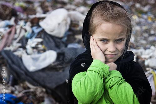 A beggar little girl in rags in a city dump close up Wallpaper Mural