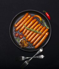 Wiener Sausages In A Pan On Black Background With Copy Space