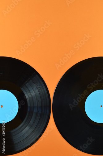 two old black vinyl records with blank cyan labels half on orange