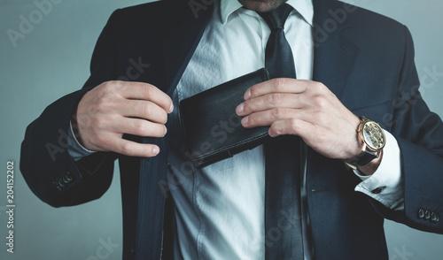 Pinturas sobre lienzo  Businessman pulls his leather wallet into suit pocket.