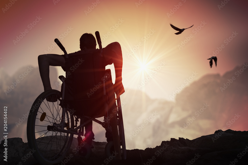 Fototapety, obrazy: Disabled handicapped man has a hope. He is sitting on wheelchair and stretching hands at sunset.